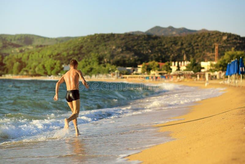 Un jeune type court le long d'une plage vide au coucher du soleil La Grèce, Chalkidiki, Sithonia images stock