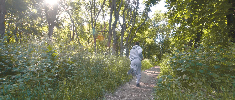 Un jeune type dans un costume gris de sports court le long du chemin parmi images libres de droits