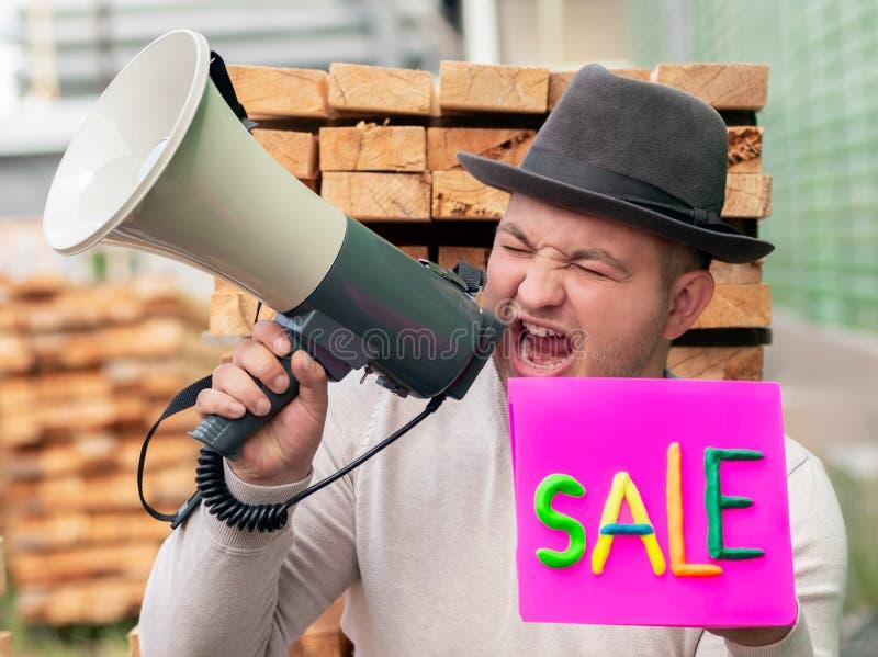Un jeune type dans des cris d'un chapeau fort dans un peuple de information de mégaphone au sujet de la vente prochaine Dans la m images libres de droits