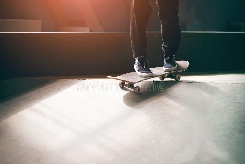 Un jeune type dans des espadrilles bleues monte une planche à roulettes sur la rampe images libres de droits