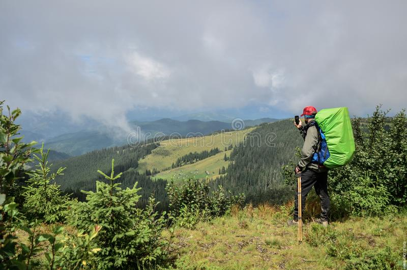 Un jeune type dans les montagnes fait une photo de se image libre de droits