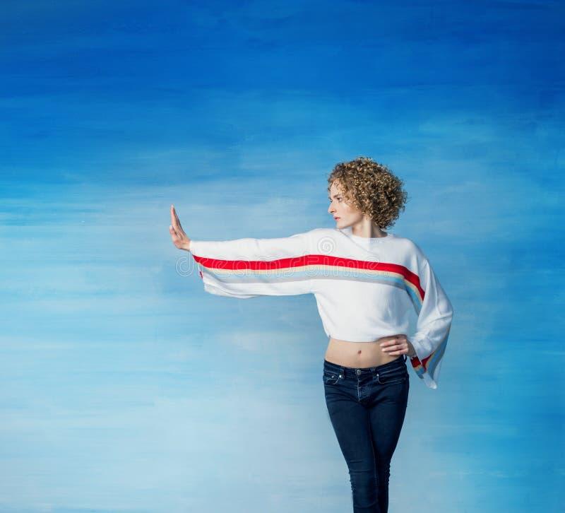 Un jeune type de transsexuel dans un arc-en-ciel blanc de chandail dans une image femelle dans la perspective d'un mur bleu montr photos stock