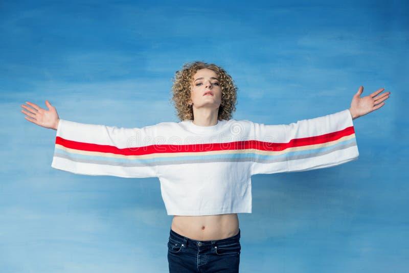 Un jeune type de transsexuel dans un chandail blanc avec un symbole d'arc-en-ciel sur un fond bleu, regards à la caméra image libre de droits