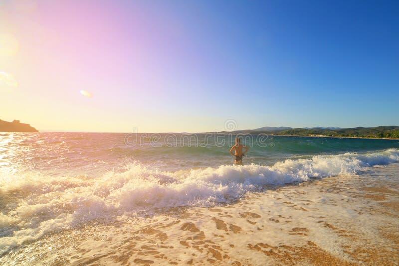 Un jeune type est entré dans la mer au coucher du soleil, un objectif grand angle tonalité La Grèce, montagnes, sithonia, voyage photo libre de droits