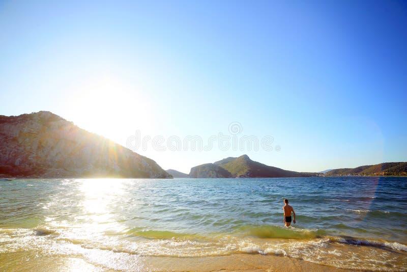 Un jeune type est entré dans la mer au coucher du soleil, un objectif grand angle tonalité La Grèce, montagnes, sithonia, voyage images libres de droits