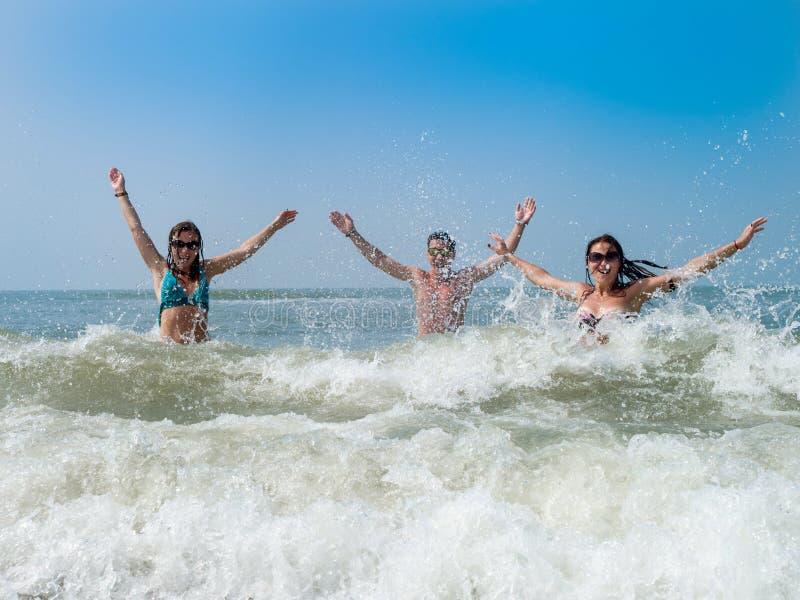 Un jeune type et amusement de deux un bel filles ?claboussant dans les vagues de l'Oc?an Indien photos libres de droits