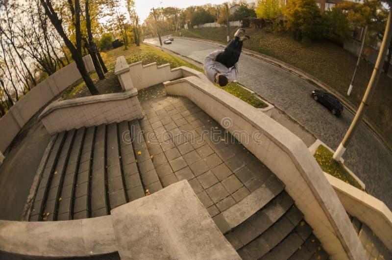 Un jeune type exécute une secousse latérale dans le parc d'automne L'athlète pratique le parkour, s'exerçant en états de rue photographie stock