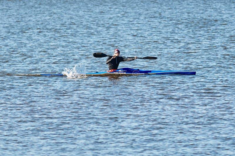 Un jeune type nage dans un canoë photos stock