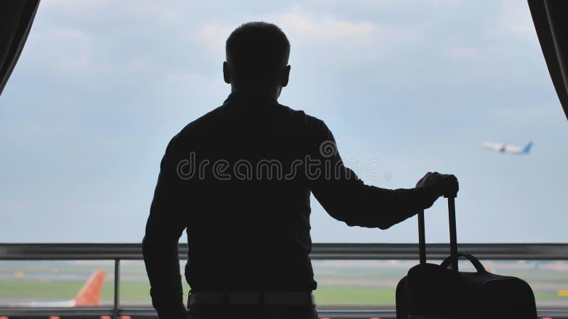 Un jeune type regarde l'avion d?collant de la fen?tre de sa chambre d'h?tel et des feuilles avec une valise pour l'embarquement images libres de droits