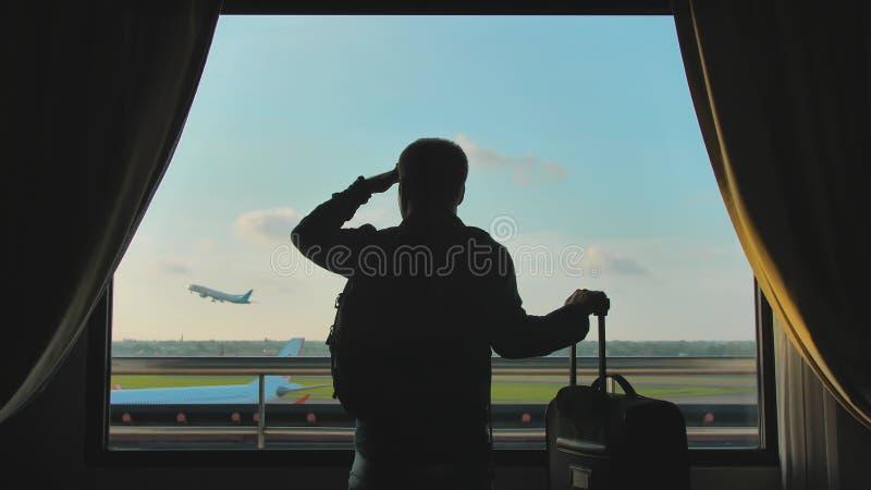 Un jeune type regarde l'avion d?collant de la fen?tre de sa chambre d'h?tel et des feuilles avec une valise pour l'embarquement photos stock