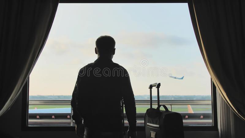 Un jeune type regarde l'avion d?collant de la fen?tre de sa chambre d'h?tel et des feuilles avec une valise pour l'embarquement photo libre de droits