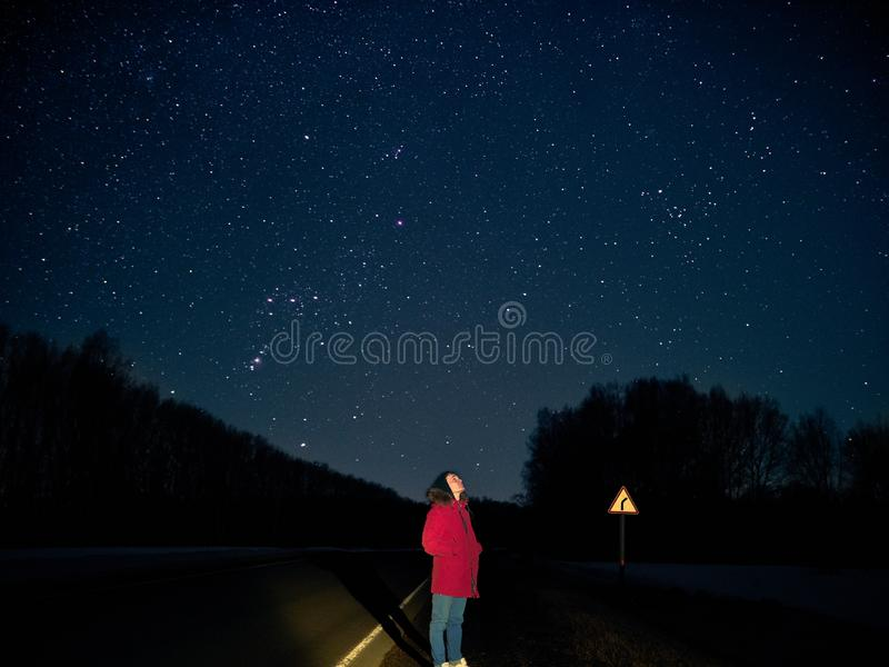 Un jeune type se tient à la nuit au bord de la route dans une veste rouge et aux regards au ciel pointillé avec des étoiles photo libre de droits