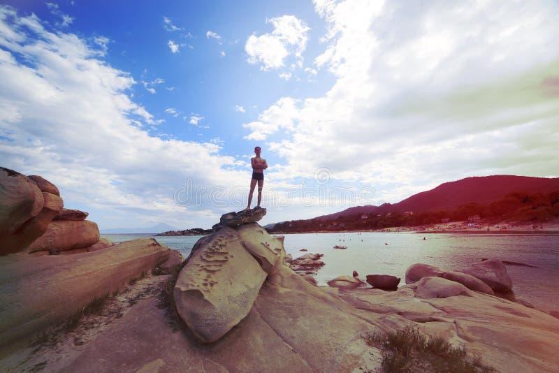 Un jeune type se tient sur une roche dans la perspective de la mer La Grèce, Chalkidiki, teintant photos libres de droits