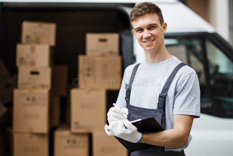 Un jeune uniforme de port de sourire bel de travailleur se tient à côté du fourgon complètement des boîtes tenant un presse-papie photographie stock libre de droits