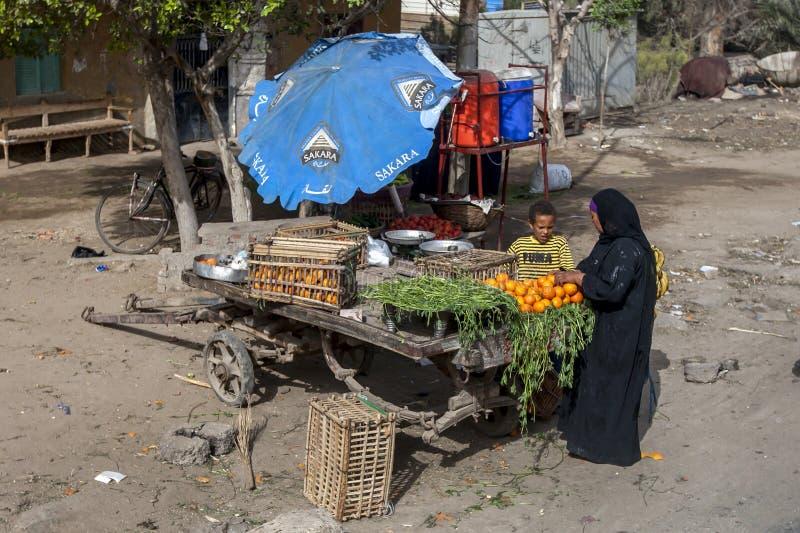 Un jeune vendeur de fruit avec un client sur les périphéries du Caire en Egypte photo stock