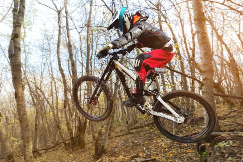 Un jinete joven en la rueda de su bici de montaña hace un truco en el salto en el trampolín de la montaña en declive foto de archivo