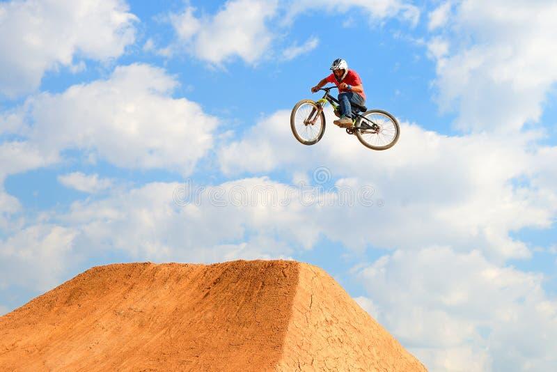 Un jinete profesional en la competencia de MTB (montaña Biking) en la pista de tierra en los deportes extremos Barcelona de LKXA imagen de archivo