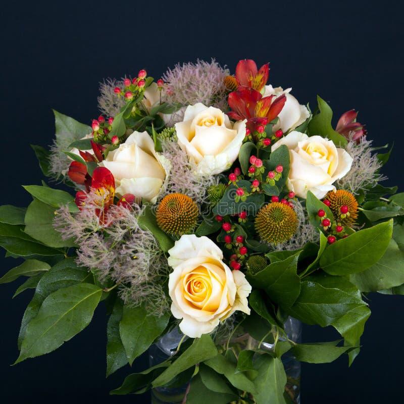 Un joli groupe de roses blanches et de fleurs rouges dans un vase en verre image stock