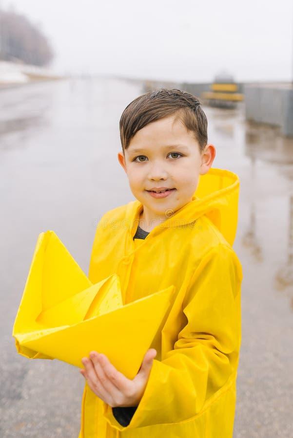 Un jouet de bateau de grand papier dans les mains d'un garçon heureux en jaune photo stock