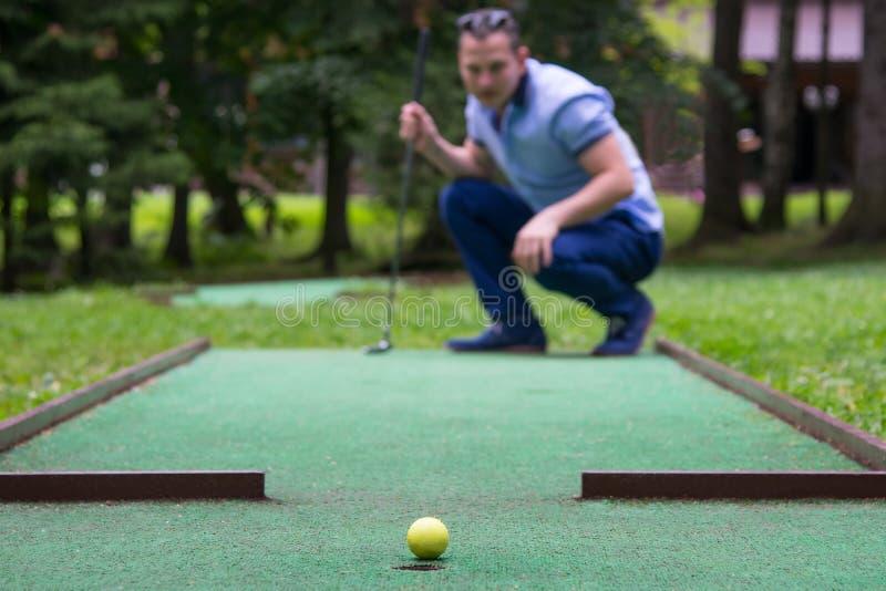 Un joueur de mini-golf regarde le résultat d'un coup au côté de la poche image libre de droits