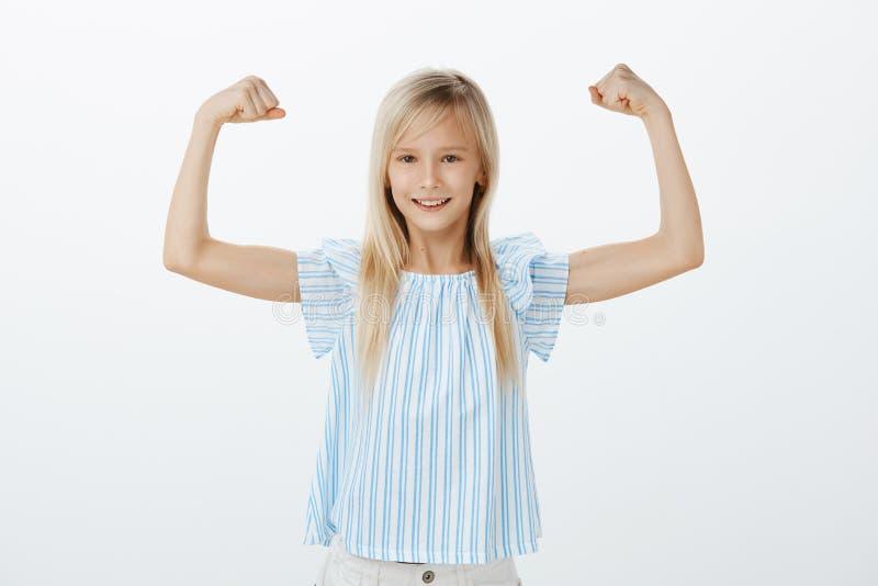 Un jour la fille deviennent sportive célèbre Peu enfant sûr avec les cheveux blonds dans le chemisier bleu, soulevant des mains a photos libres de droits