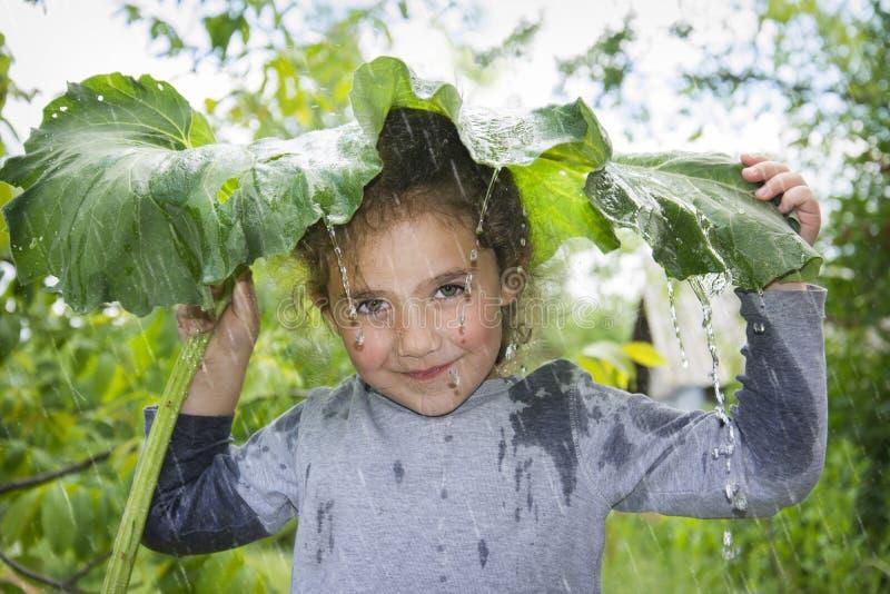 Un jour pluvieux d'été, une petite fille se cache de la pluie sous a photos libres de droits