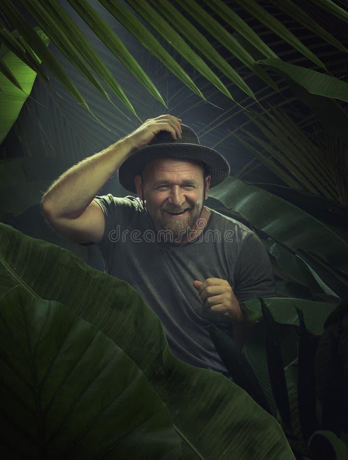 Un joven agradable que explora el ambiente de la jungla foto de archivo