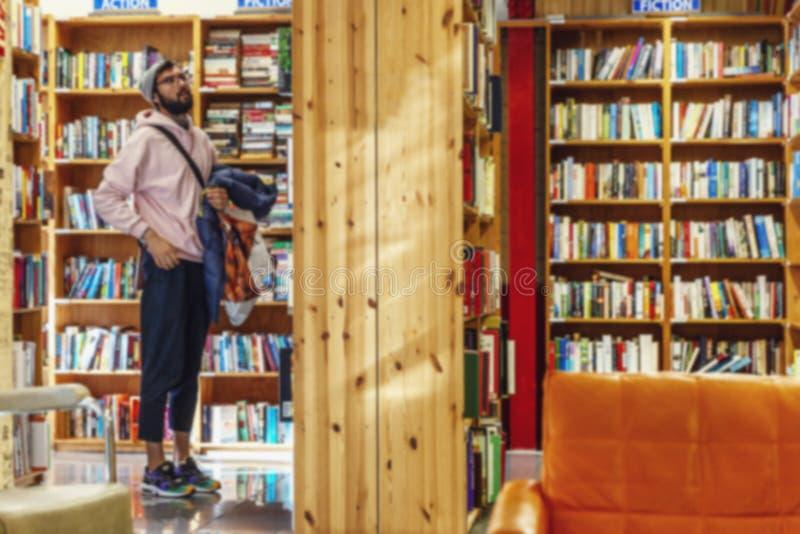 Un joven busca literatura en una librería Desenfocado fotografía de archivo