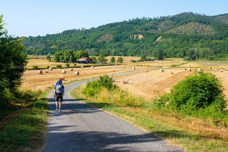 Un joven con mochila camina en un paisaje natural toscano con una carretera a través de los campos, un día soleado en junio de 2 fotos de archivo