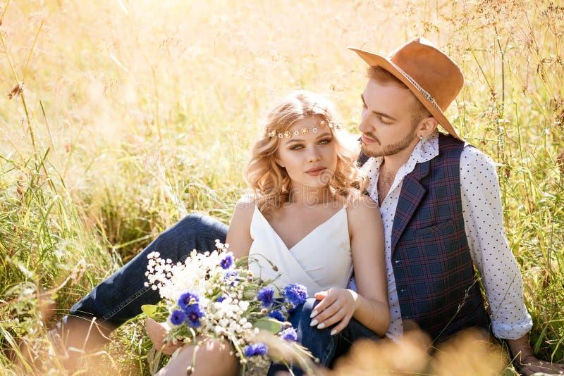 Un joven con sombrero y una chica hermosa con maquillaje y peinado, abrazándose en un campo en el césped en un día soleado imagenes de archivo