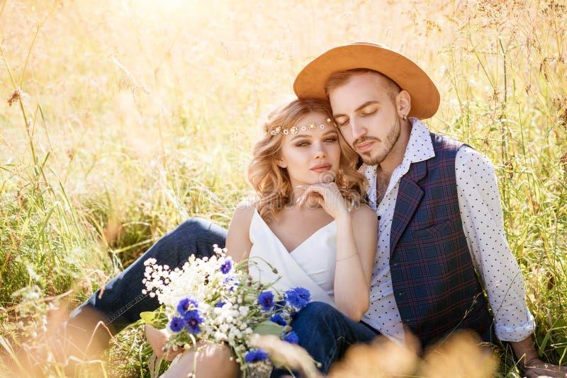 Un joven con sombrero y una chica hermosa con maquillaje y peinado, abrazándose en un campo en el césped en un día soleado fotos de archivo