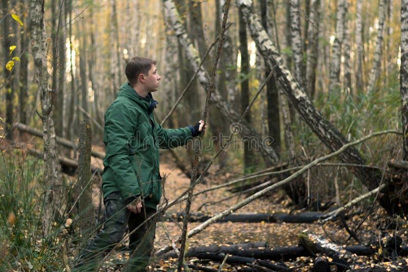 Un joven en el bosque sosteniéndose en un tallo Prendas de vestir, pantalones de caqui, chaqueta verde con un cópula foto de archivo