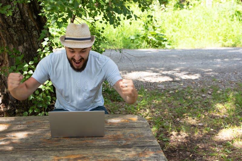 Un joven grita de alegría, mira una computadora, una laptop. Celebra la victoria. Ganó la lotería, bote imágenes de archivo libres de regalías