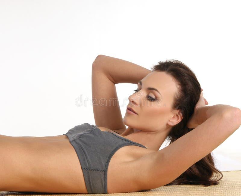Un joven y una hembra deportiva está haciendo ejercicio del ABS foto de archivo