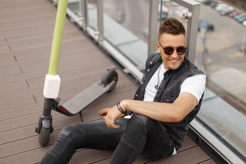Un joyeux jeune homme hipster souriant dans un gilet de denim branché en lunettes de soleil en jeans en chaussures se détend assi photos stock