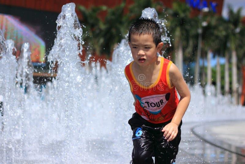 Un juego asiático del muchacho por la fuente de agua imagenes de archivo