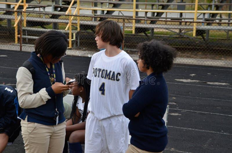 Un jugador de fútbol de la escuela secundaria consigue preguntado por un reportero para el periódico escolar fotografía de archivo libre de regalías