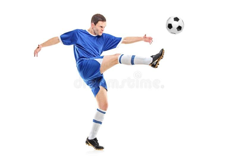 Un jugador de fútbol que tira una bola fotos de archivo libres de regalías