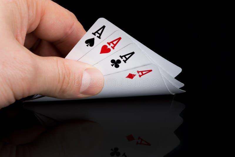 Un jugador de póker mira sus tarjetas aumentándolas en una tabla negra imagen de archivo libre de regalías