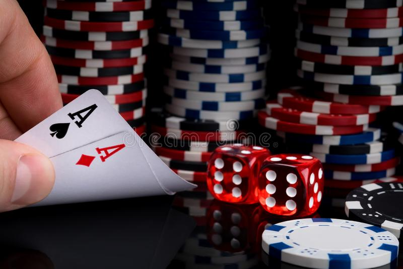 Un jugador de póker mira sus tarjetas aumentándolas en una tabla negra contra la perspectiva de pilas de fichas de póker al lado  imagen de archivo libre de regalías
