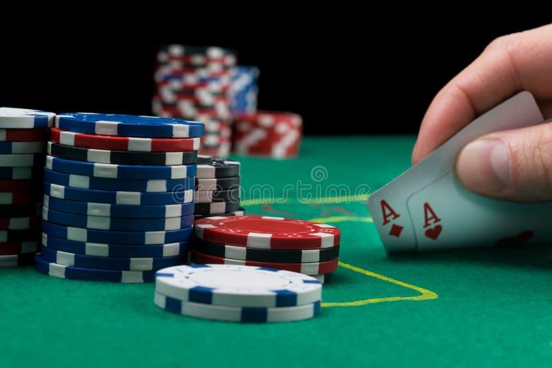 Un jugador de póker mira sus tarjetas levantándolas en las fichas de póker de una tabla verde está en la pila al lado de ellas fotografía de archivo