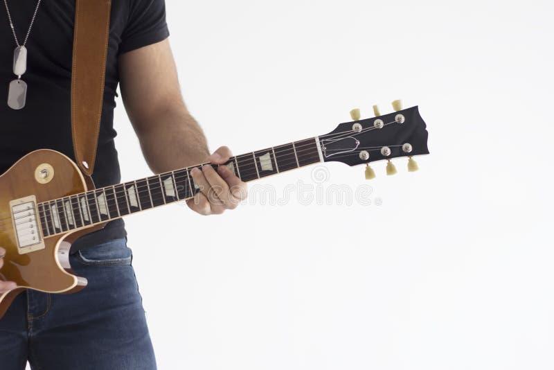 Un jugador eléctrico del guitarrista del hombre caucásico que juega en la silueta del estudio aislada en el fondo blanco foto de archivo