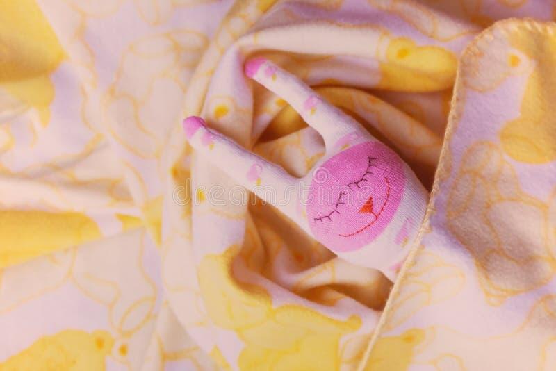 Un juguete blanco, rosado, una liebre linda est? mintiendo debajo de una manta imagenes de archivo