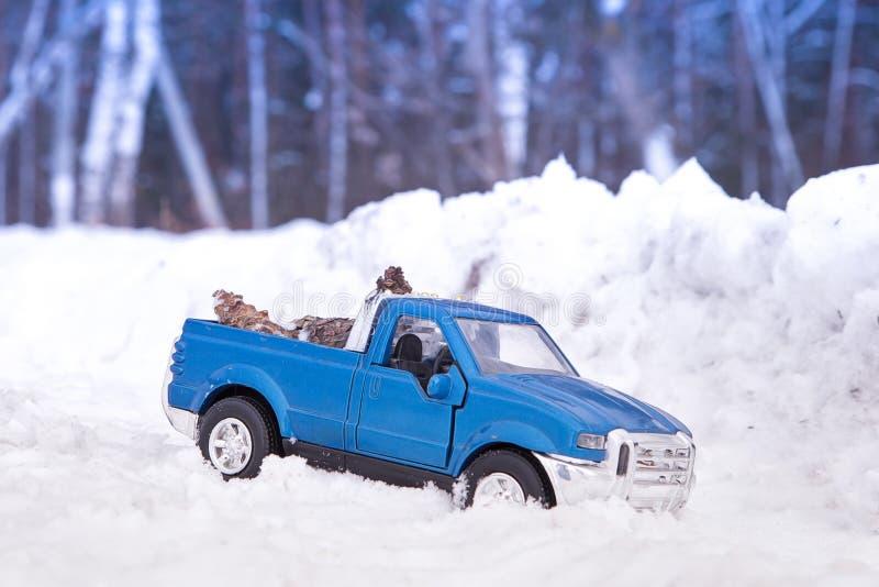 Un juguete Camioneta pickup azul en bosque del invierno en nieve acumulada por la ventisca Conos de abeto que llevan en la parte  imagen de archivo