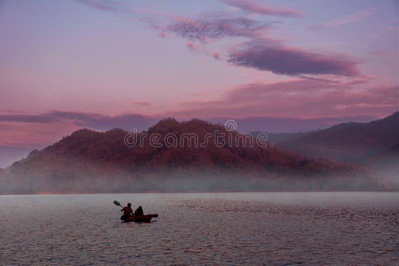 Un kayak di due genti sul tramonto fotografia stock