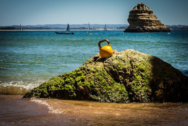 Un Kettlebell sur une roche à la plage image stock
