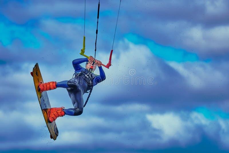 Un kitesurfer dell'uomo fa un salto contro lo sfondo di un cielo bianco blu nuvoloso immagini stock libere da diritti
