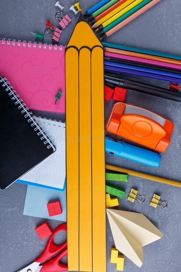 Un lápiz de papel amarillo grande miente en los diversos lápices, cuadernos, abrazaderas y creyones dispersados imagen de archivo