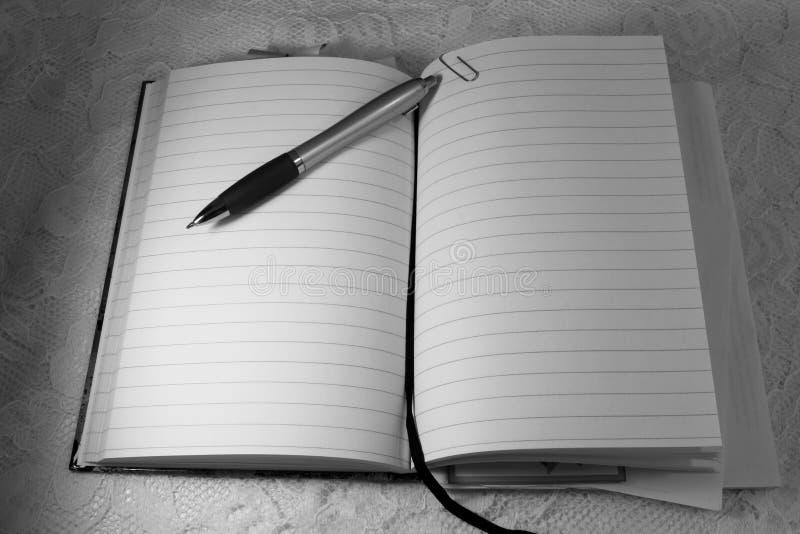 Un lápiz del bolígrafo miente encima de un libro abierto del diario foto de archivo