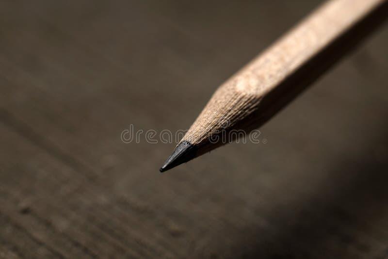 Un lápiz negro del grafito en el fondo de madera imágenes de archivo libres de regalías